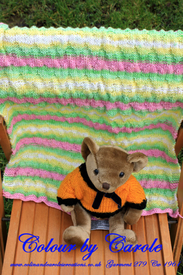 Chevron baby blanket, in colours of pastel shades of pink, pale yellow and green and white. A lovely soft hand knitted baby blanket in colours of pastel shades of pink, pale yellow and green and white. The main part of the blanket has a chevron pattern knitted into it with the border contrasting in garter stitches.
