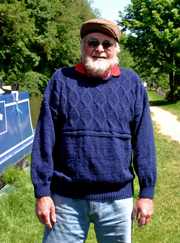 A Modern Boatman's gansey hand knitted by Carole Wareing of Colin and Carole's Creations and The Wool Boat.  This gansey Carole knitted to her own pattern. It is called a modern boatman's gansey as it was knitted in a modern style that while it is based on the basic principles of a gansey it is knitted on two needles and then the pieces are sewn together. Traditionally Ganseys where knitted in the round on a set of 5 needles.    This garment has been created from an acrylic yarn in a navy blue shade which was the colour traditional fishermen's gansey where knitted in for everyday use. The yarn for this garment is James C Bretts Top value double knitting weight yarn.  Garment 001  This is a self portrait by Colin Wareing  Image Cw 5080 copyright Colin Wareing of Colin and Carole's Creations #wool #yarn #knitting #Gansey #Hand knitting #commissioned knitting