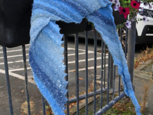 """A shades of blue dragon tooth scarf hand knitted aboard the narrow boat """"Emma Maye"""" in Lancashire by Carole Wareing of Colin and Carole's Creations. This unique garment is an adult sized scarf, knitted from Northern Lights yarn. Carole is creating these shawls as """"Hand made hugs"""" that can be use to send love to someone you can't visit at the moment."""