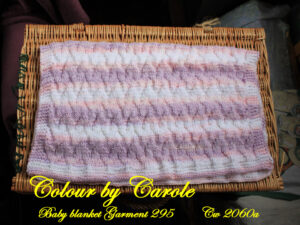 Chevron baby blanket in pastel shades of pinks, lilac, and whites.