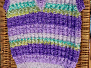 "A child's sleeveless jumper hand knitted by Carole Wareing, this is Carole of Colin and Carole's Creations based on a narrow boat named ""Emma Maye"" and also known as The Wool Boat that is based on the Leeds and Liverpool canal in Burscough in West Lancashire."