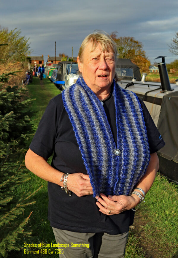 "A neck scarf hand knitted aboard the narrow boat ""Emma Maye"" in Lancashire by Carole Wareing of Colin and Carole's Creations. This one is knitted in a yarn that is in shades of blue and grey."