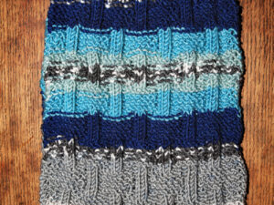 An adult sized scarf hand knitted by Carole Wareing from Colin and Carole's Creations. The scarf has a basket weave pattern knitted into the final 9 inches, at either end, whilst the yarn produces a natural striped pattern.