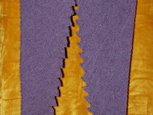 "Mauve Dragon tooth shawl. A Dragon tooth scarf hand knitted aboard the narrow boat ""Emma Maye"" in Lancashire by Carole Wareing of Colin and Carole's Creations. This unique garment is an adult sized shawl, knitted from a yarn available from The Wool Boat which is produced by James C Brett. The yarn used for this shawl is an acrylic and merino mix yarn from the James C Brett's DK with Merino range The colour is a shade of mauve, shade DM13."