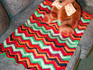 A lovely soft baby blanket hand knitted in bright colours red, orange, green and black. The blanket has a chevron pattern. The blanket measures 45cm by 65cm