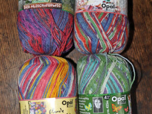 4 lovely balls of Opal 4 ply sock yarn from The Wool Boat. We have 2 balls of each of these shades, so chance to grab a pack of all 4 balls for £32. This price includes free delivery to a uk address. These 4 balls, are top left, Purple/Orange, Schafpate 1X Shade no 9412, dye 1716, Top right, Multi coloured, Potpourri; Shade no 8840 dye 1114, Bottom left, Pastel, Rainbow, Claude Monet, Shade no 6980 dye no 2184 Bottom right, Greens and blues, Butterfly, Shade 9653 Dye no 2070