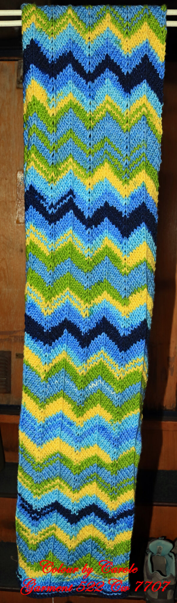 """Blue, Yellow and green chunky scarf. A long and warm bright scarf designed and hand knitted by Carole Wareing of Colin and Carole's Creations and The Wool Boat. This is an adult sized garment, knitted from a chunky yarn, with a chevron pattern in shades of Blue, Yellow and Green. It is ideal for keeping warm on a windy winter's day whilst doing some gardening, locking, bicycling, standing markets, fishing, watching outdoor sports and events, or walking and rambling. The garment is approx 72 inch long and 11 inches wide. The scarf is for sale for £25 from the Wool Boat The warmer is knitted from J C Bretts """"Party Time"""" chunky knitting acrylic yarn Shade PT 2 which has bold Blue, Yellow and green shades in it. The yarn knits to most chunky knitting patterns and is available from the Wool Boat of which we have a range of 7 other shades at £3.50 per 100 gram ball. Posted out would be for £30 including delivery to a uk address, Copyright Colin Wareing Garment 522 Cw 7707"""